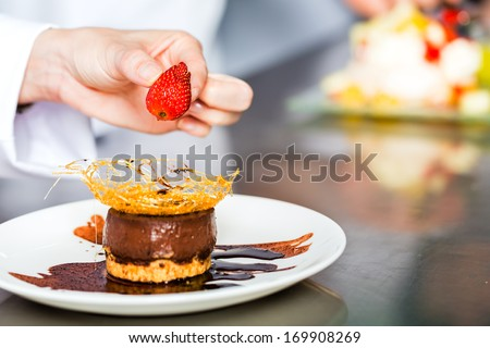 Asian Indonesian chef along with other cooks in restaurant or hotel kitchen cooking, finishing a dish or plate for dessert - stock photo