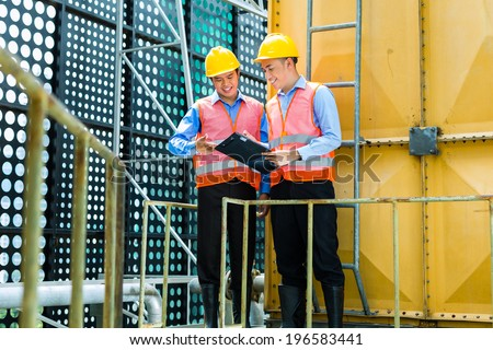 Asian Indonesian construction workers with helmet and safety vest on a building or industrial site in Asia - stock photo