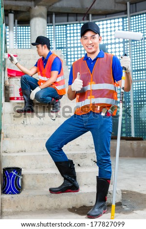 Asian Indonesian painter paint with a brush, paint roller, color and tools in gumboots or rubber boots and protection gloves the walls of a tower building or construction site - stock photo