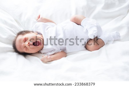 Asian infant baby lying on white bed background - stock photo