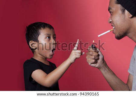 Asian kid asking a smoker to stop smoking shot over red background - stock photo