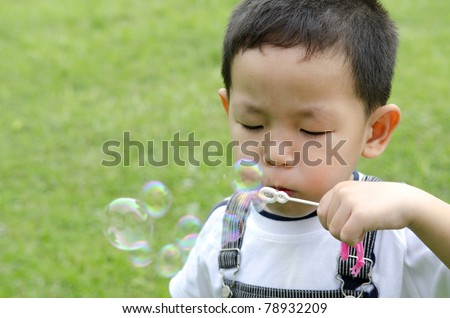 asian kid blowing soap bubble - stock photo