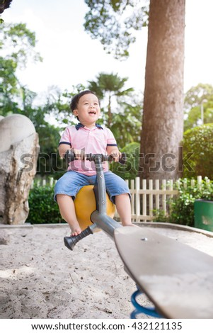 Asian kid boy playing in the playground. He is playing seesaw and laughing in a park in the city. The idea of education and health. Children energetic and intelligent. - stock photo