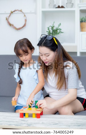Asian kid girl and mother playing toy block; together with cheerful and happy in living room, activity in family.