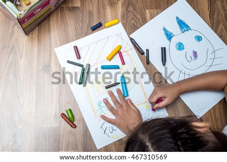 Asian Kid Girl Drawing On Paper With Crayons