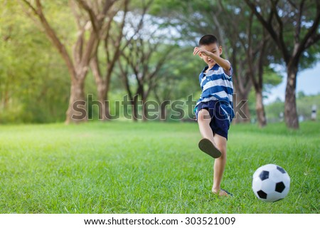 asian kid playing soccer in the park, Authentic action kicking ball