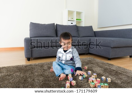 Asian kid playing toy block at home - stock photo