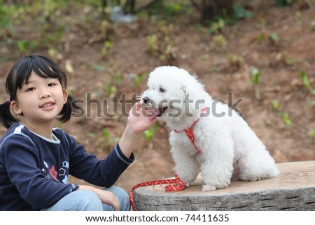 Asian kid playing with a toy poodle dog - stock photo