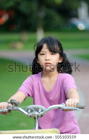 Asian kid riding bike in the park at sunset - stock photo