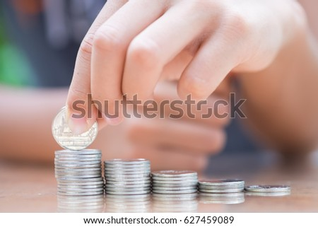 Asian kid's hand putting coins to stack of coins. Concept of money saving, financial.