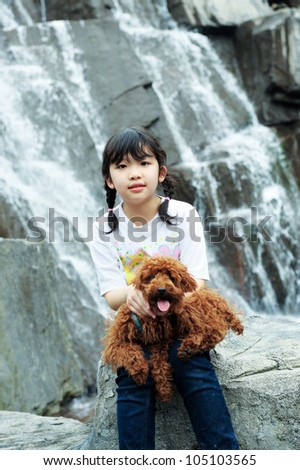 Asian kid sitting and holding an poodle dog near the waterfall - stock photo