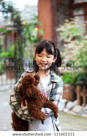 Asian kid standing and holding poodle dog - stock photo