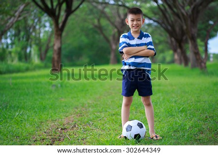 asian kid standing with soccer ball in the park - stock photo
