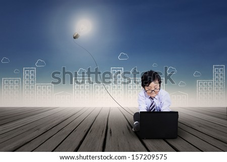 Asian kid with business clothing working on laptop. Background is scribble of cityscape - stock photo