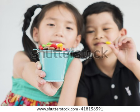Asian kids are playing with candy. Photo is focused at candy.