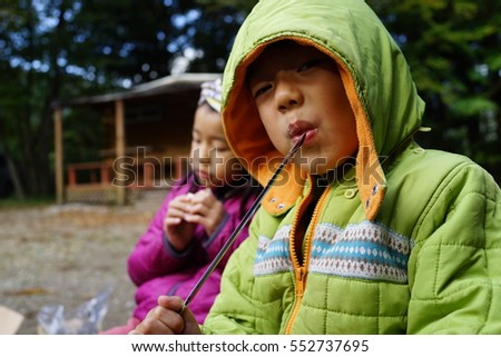 asian kids eating marshmallow at camp BBQ