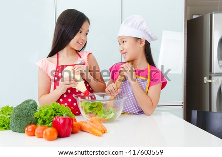 Asian kids enjoyed cooking in the kitchen - stock photo