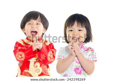 Asian kids in greeting gesture. Chinese new year concept.