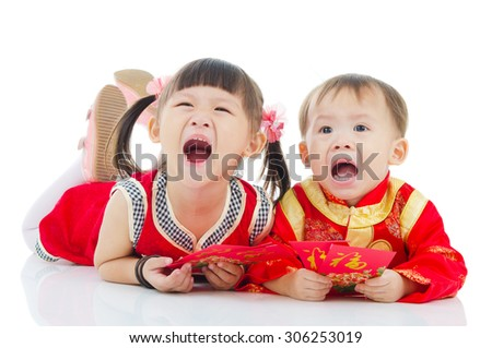 Asian kids in traditional chinese costume, cheongsam lying on the floor holding red packet