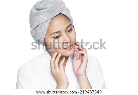 Asian lady inspecting her facial skin. Isolated in white background.