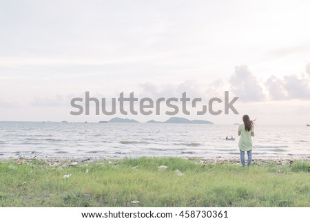 Asian lady looking at ocean, thinking her goal.