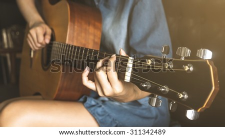 Asian Lady playing guitar with vintage look - stock photo