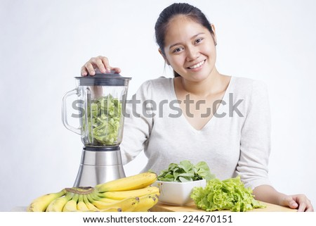 Asian lady preparing fruits and vegetables for making green smoothie. - stock photo