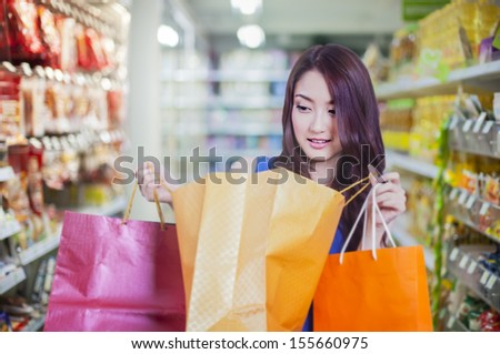 asian lady with shopping bag in supermarket - stock photo