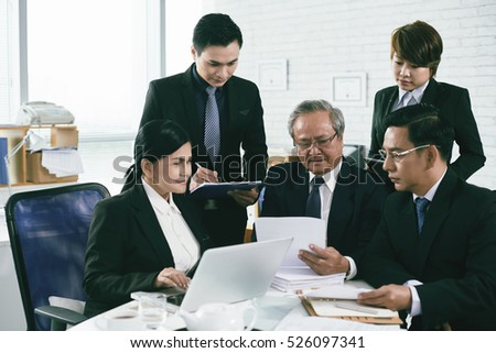 Asian lawyers working with documents during meeting