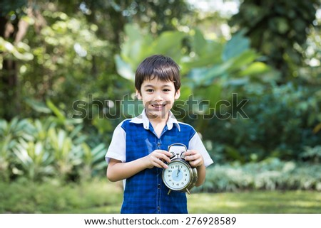 Asian little boy hold a clock and smile in park - stock photo