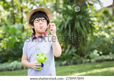 Asian little boy is blowing a soap bubbles with smile face in park - stock photo