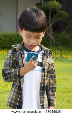 Asian little boy playing and calling Smart-phone - stock photo