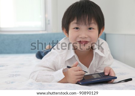 Asian little boy playing game at his bedroom