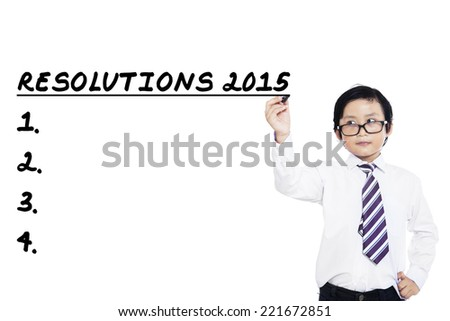 Asian little businessman writes his resolutions in 2015, isolated over white background - stock photo
