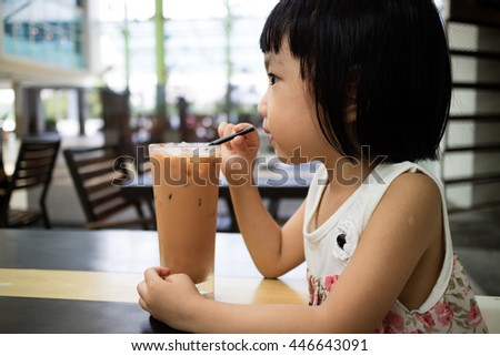 Asian Little Chinese Girl Drinking Ice Milk Tea in Outdoor Cafe - stock photo