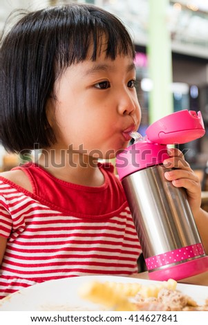 Asian Little Chinese Girl Drinking Water from Stainless Steel Bottle in Outdoor Cafe
