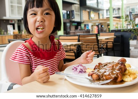 Asian Little Chinese Girl Eating Western Food in Outdoor Cafe - stock photo