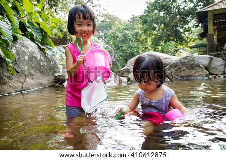 Asian Little Chinese Girls Playing in Creek in the Forest