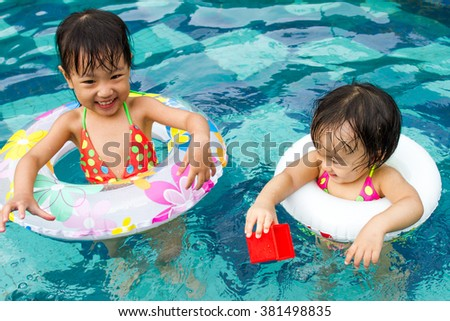 Asian Little Chinese Girls Playing in Swimming Pool with Swimming Circle - stock photo