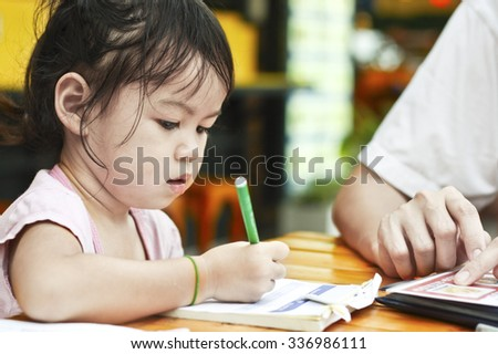 Asian Little Girl are Writing on Notebook.