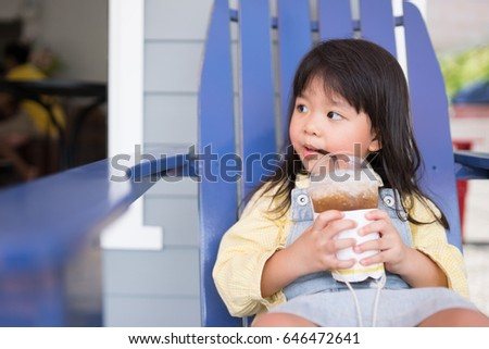 Asian little girl drinking lemon tea in outdoor cafe on summer.