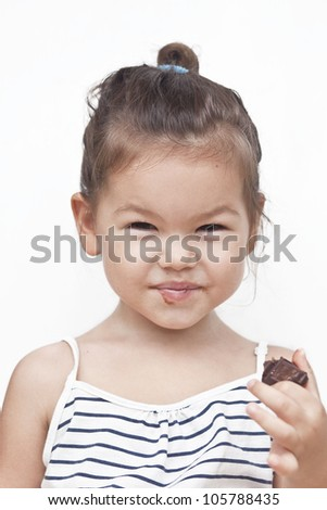 Asian little girl eating chocolate