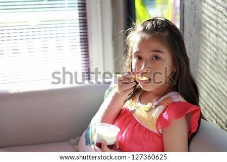 asian little girl eatting yogurt - stock photo
