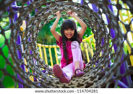 Asian little girl enjoys playing in a children playground, Outdoor portrait - stock photo