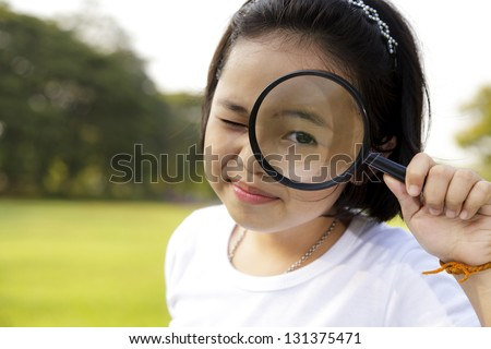 Asian little girl holding a magnifying glass in outdoor - stock photo