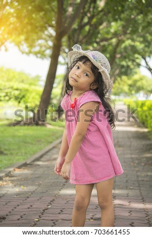 asian little girl in pink suit and cap in the garden outdoor