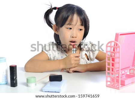 asian little girl is applying make up her face isolated in white background
