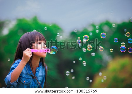 Asian little girl is blowing a soap bubbles - stock photo