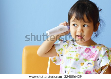 Asian Little Girl Measures Temperature on Blue Background. - stock photo