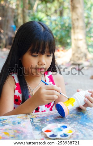 Asian little girl painting in the park  - stock photo